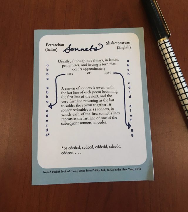 A card with instructions for writing sonnets, from A Pocket Book of Forms, on a table next to an ink pen