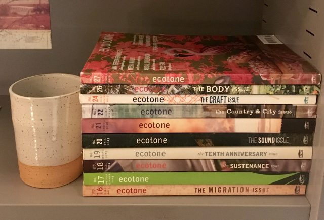 A bookshelf with a stack of copies of ecotone and a stoneware mug